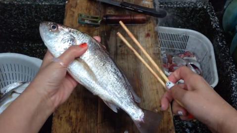魚に割り箸を突っ込む